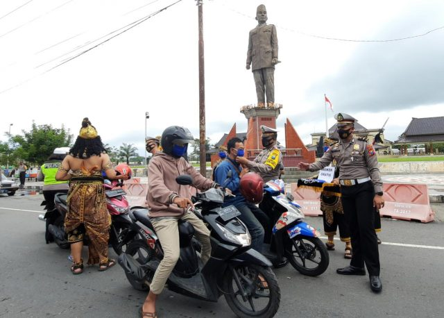 Kasatlantas Polres Blitar bersama petugas yang berpakaian Gajah Mada membagikan masker gratis kepada para pengguna jalan yang melintas di depan Kantor Bupati Blitar Jalan Kusuma Bangsa Kecamatan Kanigoro