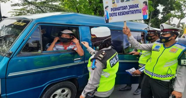 PROKES: Anggota Polwan Polres Malang saat sosialisasi Prokes Covid-19 kepada masyarakat pengendara kendaraan.