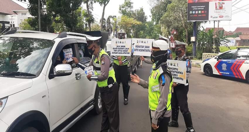 SOSIALISASI: Anggota Satlantas Polres Malang saat membagikan brosur sosialisasi Operasi Zebra Semeru 2020.