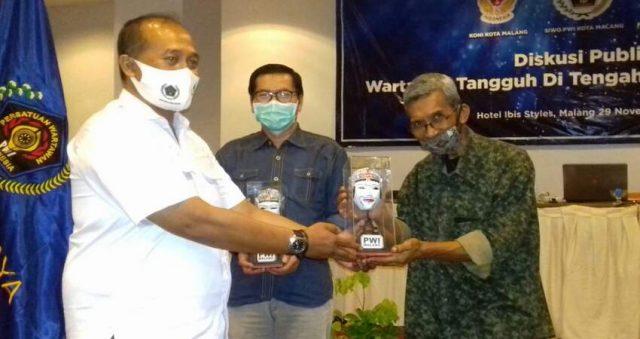 CENDERAMATA: Ketua PWI Malang Raya M Ariful Huda saat memberikan cenderamata kepada narasumber sekaligus wartawan senior Yunanto.
