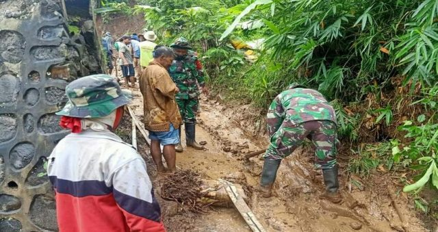 TURUN: Danramil 0818/03 Kasembon Kapten Arm Budi bersama warga masyarakat saat menyingkirkan material tanah longsor di Desa Pait.