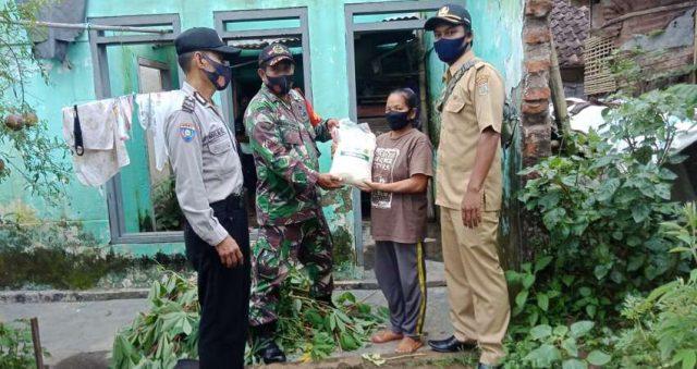 BANTUAN: Anggota Koramil 0818/16 Sumawe bersama anggota Polsek Sumawe saat menyalurkan bantuan sembako kepada masyarakat Desa Druju.