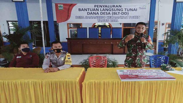 KAWAL: Anggota Koramil 0818/14 Turen saat menyampaikan pentingnya Prokes Protokol disela-sela penyaluran dana BLT.